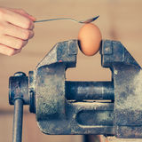 Detail of Hand with Spoon Tapping an Egg Fixed in Vice (color to Stock Images