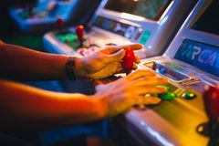 Detail on Hands with Arcade Joystick Playing Old Arcade Video Game. In a dark gaming room Royalty Free Stock Photo