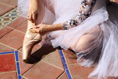 Detail of hands of a ballet dancer putting on and fastening her pink ballet shoes. Concept dance and classical ballet
