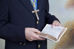 Detail of the hands of a boy dressed in a blue communion suit. Detail of the hands of a bay dressed in a blue communion suit, holding a book, a rosary and royalty free stock photo