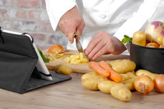 Detail of hands of chef slicing potatoes Royalty Free Stock Photography