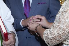 Detail of the hands of a couple at the time she puts the ring to him stock images
