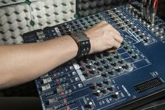Detail of the hands of a man manipulating a mixing desk. Music concept. Detail of the hands of a man manipulating a mixing desk royalty free stock images