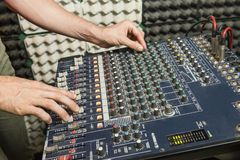 Detail of the hands of a man manipulating a mixing desk. Music concept. Detail of the hands of a man manipulating a mixing desk royalty free stock image