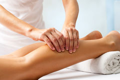 Detail of hands massaging human calf muscle. Stock Images