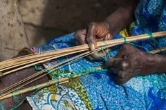Detail of the hands of an old woman working in front of her hut at the village of Eticoga in the island of Orango. Guinea Bissau royalty free stock photo