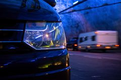 Detail of a headlamp of a modern van at the night. With a speeding caravan in the blurred background stock images