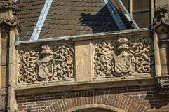 Detail of high relief stone sculpture of coat of arms in old church facade of Amsterdam. The city is famous for its huge cultural activity, graceful canals and Royalty Free Stock Photography
