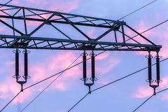 Detail of a high voltage power cable during sunset. Pink clouds Royalty Free Stock Photo