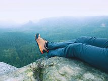 Detail of  hiker legs in black orange hiking boots on mountain summit. Feet in trekking shoes Royalty Free Stock Images