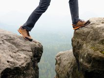 Detail of  hiker legs in black orange hiking boots on mountain summit. Feet in trekking shoes Stock Images
