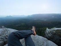 Detail of  hiker legs in black orange hiking boots on mountain summit. Feet in trekking shoes. Detail of  hiker legs in black orange hiking boots on mountain Stock Image