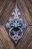 Detail of a historic knocker on the door. Made in the Czech Republic. The handpiece is a circular shaped gobelin impinging on a metal anvil or plate on the Stock Photos