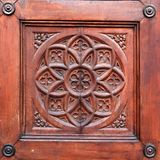 Detail of historical wooden door. Closeup view of a wooden door of some historical European building. The door is handcrafted.nThe theme is is a rosette and Stock Photos