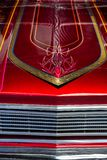 Detail of the hood of a red and chrome car with hand-painted lines royalty free stock photo