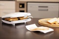 Making hot sandwiches in a sandwich maker stock photos