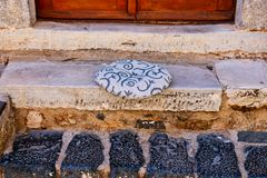 Round Cushion on Marble Step, Monemvasia, Greece. Detail of a house front step and doorway, Monemvasia, Peloponnese, Greece, with a soft round cushion on a royalty free stock photography