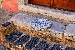 Round Cushion on Marble Step, Monemvasia, Greece. Detail of a house front step and doorway, Monemvasia, Peloponnese, Greece, with a soft round cushion on a royalty free stock photo
