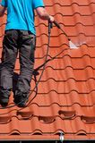 Worker cleaning metal roof with high pressure water royalty free stock images