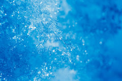 Detail of ice crystal and snowflakes, blue background Royalty Free Stock Image