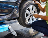 Detail image of mechanic hands with tool, changing tyre of car Royalty Free Stock Photos