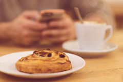 Detail image of unrecognisable man drinking coffee and holding smart phone while having breakfast in restaurant. Stock Image