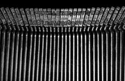 Macro detail of typescript inside electric typewriter. Detail of the individual hammers with engraved text and typescript inside electric typewriter Royalty Free Stock Image