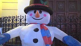 A video useful to express a concept about winter, snowman, church, cheerfulness, or festivity.