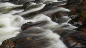 Detail intimate landscape image of river flowing over rocks with. Detail landscape image of river flowing over rocks with long exposure motion blur stock images