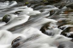 Detail intimate landscape image of river flowing over rocks with. Detail landscape image of river flowing over rocks with long exposure motion blur stock photo