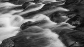 Detail intimate landscape image of river flowing over rocks with. Detail landscape image of river flowing over rocks with long exposure motion blur royalty free stock photo