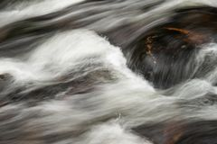 Detail intimate landscape image of river flowing over rocks with long exposure motion blur. Detail landscape image of river flowing over rocks with long exposure royalty free stock photography