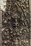 Detail of Intricately Carved Bas Relief in Hindu Temple. Detail of Intricately Carved Bas Relief featuring repeating vine pattern and figure in center, found in Stock Images