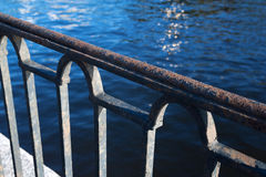 Detail of iron fence with spider web waterfront Stock Photo
