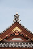 Detail on japanese temple roof against blue sky. Stock Photography
