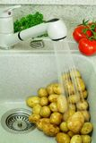 Detail in kitchen – potatoes in washing-up bowl Stock Images