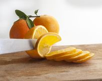 Detail of a knife cutting a slice of orange on a wooden board. Detail of a knife cutting some slices of orange on a wooden board with more whole rakes stock images