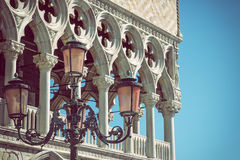 Detail of lamp and columns in Venice. Horizontally. Detail of columns and lamp of the Doge`s palace in Venice Italy with blue sky in the background. Edited as a Royalty Free Stock Photos