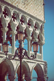 Detail of lamp and columns in Venice. Vertically. Detail of columns and lamp of the Doge`s palace in Venice Italy with blue sky in the background. Edited as a Royalty Free Stock Image