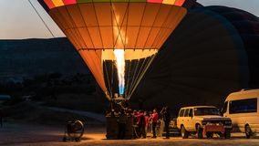 Detail of a large hot air balloon being inflated with fire at dawn. Detail of a large hot air balloon being inflated at dawn for its initial flight Stock Images