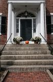 Large US colonial style house entrance seen in New England. Detail of the large pillars, porch and the usual undulating path leading to the steps is clearly Royalty Free Stock Photos