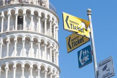 Detail of the leaning tower with directions to the ticket office, bathrooms and video surveillance notice. PISA, IT - MARCH 28 2019; Detail of the leaning tower royalty free stock image