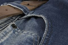 Detail of leather belt on a blue jeans Royalty Free Stock Image