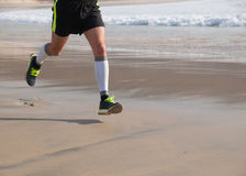 Detail of the legs of an athlete running on the beach Stock Photo