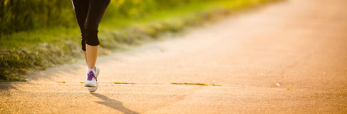 Detail of legs of a female runner on road Stock Photos