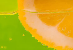 Detail of a lemon in a glass on green background Stock Photo