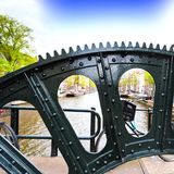 Lifting Gear of Drawbridge. Detail of the lifting gear of drawbridge over the canal in Amsterdam. Street View with bikes, boats and city life through the Stock Photos