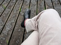 Adult male legs seen crossed while sitting on a park bench. Detail of the light coloured trousers, stripped socks and formal, black shoes are visible. The Royalty Free Stock Photography
