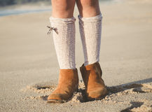 Detail of little girl boots on the beach Stock Photo