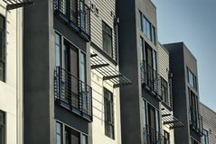 Detail of living units or flats in a residential apartment building. Modern industrial look with metal awnings and siding of a stylized building for residential Stock Photos